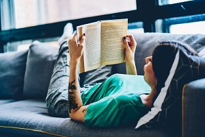 Female reading book on sofa at home