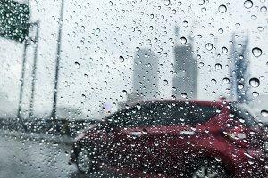 Raindrops on car glass at city