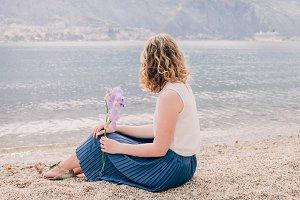 romantic woman sit on beach with flo