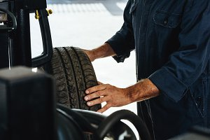 Mechanic checking car tire condition