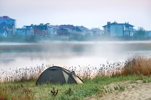 Green tent near river with morning m