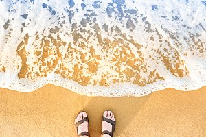 Woman's feet in sandals on a beach s