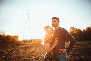 guy and girl in the field on the sun