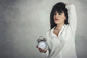 Sleeping woman holding clock