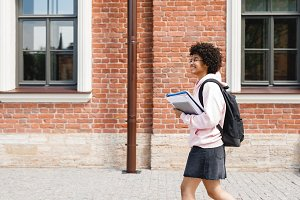 Smiling girl walking with books