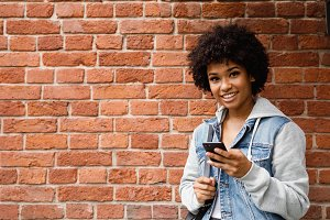 Smiling girl holding mobile phone