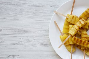 Grilled pineapple on bamboo sticks