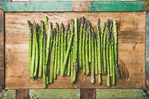 Raw uncooked green asparagus in row