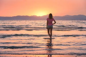 Young woman in the sea at sunset