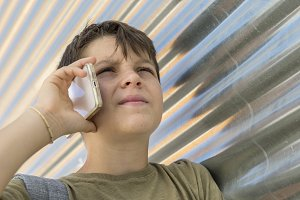 Cheerful boy using a mobile phone