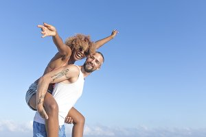 Couple piggy back on the beach in th