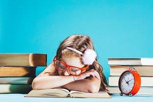 Little girl sleeping on an open book