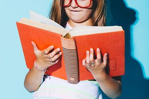 Little girl reading a book, wearing