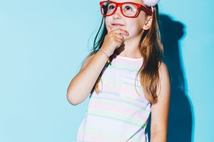 Little pensive girl in red glasses r