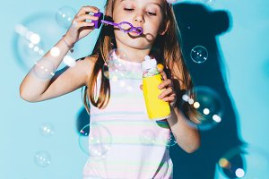 Little girl blowing soap bubbles on