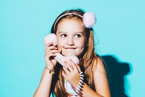 Little girl using pink analogue phon