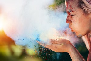 Woman blowing colorful holi powder