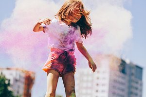 Little girl playing in colorful clou