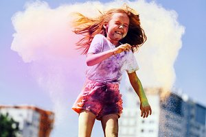 Little happy girl playing with color