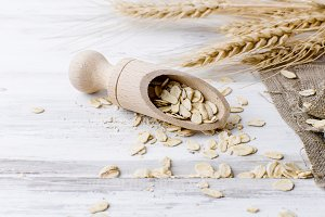 Oat flakes in wooden scoop on dark