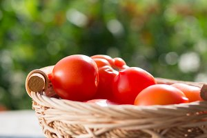 Red tomatoes in a basket on a natura
