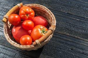 Ripe juicy red tomatoes on black woo
