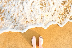 Woman's feet on yellow beach sand