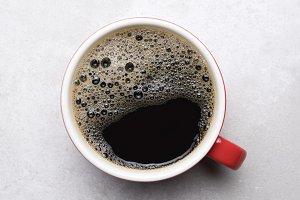 Black Coffee in Red Mug on Gray Tile