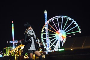 Young woman at funfair at night