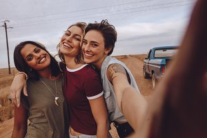 Women on road trip taking selfie