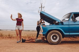 Women with broken down car on road