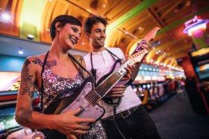 Couple playing guitar arcade game