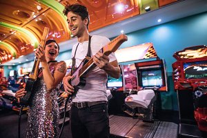 Excited couple holding gaming guitar