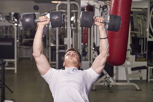 one young man, holding dumbbells, ar
