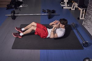 one young man, abs exercise, laying