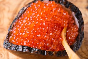 Red caviar in wooden bowl