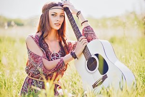 Pretty young hippie girl with guitar
