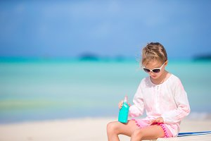 Little girl with bottle of sun cream