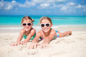 Happy kids lying on warm white sandy