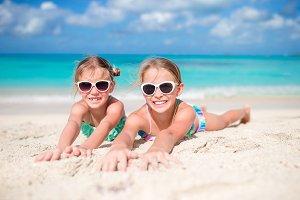 Happy kids lying on warm white sandy