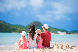 Family of four making sand castle at