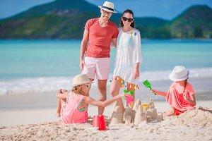Family making sand castle on white b