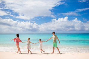 Family of four walking on white beac