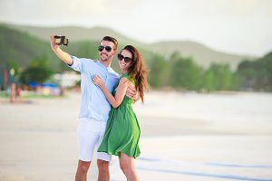 Happy couple taking a photo on white