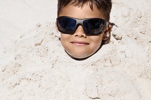 Young Boy Buried In The Sand