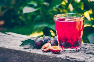 Plum juice in glass on wooden table