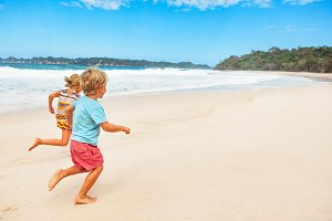 Happy kids running by tropical beach