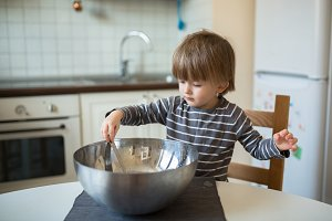 Toddler boy with  bowl in the kitche