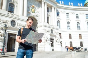 Man tourist with a city map and back