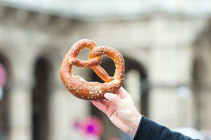 Salted pretzel in the hands of a man